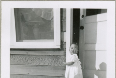 A baby in the doorway of a housing project apartment (ddr-densho-300-58)