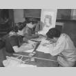 Three students doing steamed crayon work for tablecloths and wall hangings in adult crafts class at Granada incarceration camp (ddr-csujad-14-41)
