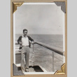 Man in a sweater leans against the rail of a ship (ddr-densho-404-258)