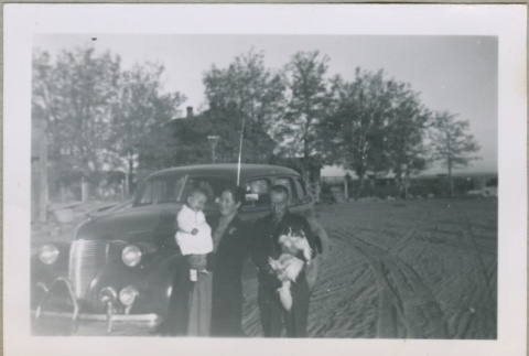 A family standing in front of a car (ddr-densho-300-35)
