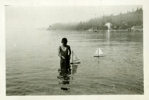 Children playing in water with sailboats (ddr-densho-182-73)