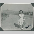 Woman walking with umbrella at Heart Mountain concentration camp (ddr-densho-321-118)