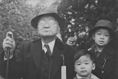 Grandfather and his grandchildren waiting to be interned (ddr-csujad-7-7)