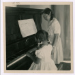 Young girl plays piano her teacher observing (ddr-densho-362-24)