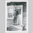 A man standing in the doorway of a housing project apartment (ddr-densho-300-59)