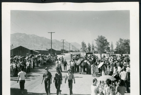 Photograph of a large group of incarcerees standing near the entrance of Manzanar (ddr-csujad-47-10)
