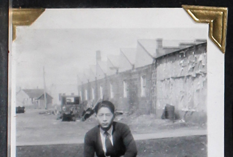 Tokeo Tagami kneels outside a row of buildings (ddr-densho-404-165)