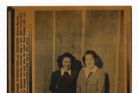 Two young women standing in front of barracks (ddr-csujad-52-22)
