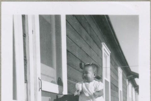 A baby standing on a chair (ddr-densho-300-50)