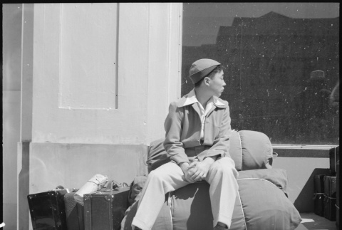 Japanese American waiting with baggage (ddr-densho-151-102)