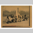 Students eat lunch in front of a monument at Manzanar (ddr-csujad-52-12)