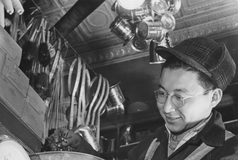 Former Los Angeles fruit and vegetable clerk Joe Sitsuda weighing nails in Union Hardware Store, Denver, Colorado (ddr-csujad-14-28)