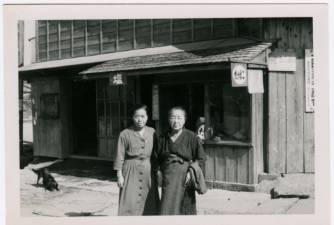 Two Japanese women stand before the front of a building (ddr-densho-348-13)