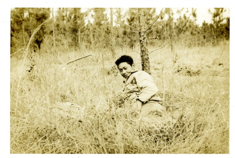 Soldier laying in a field (ddr-densho-22-228)