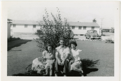 Man and two women sitting in front of camp administration building (ddr-manz-8-10)