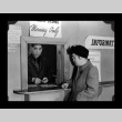 Kazuo Nikaido and incarceree at the cashier window, Amache Co-op (ddr-csujad-55-1550)