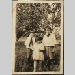 Three siblings in front of an apple tree (ddr-densho-259-9)