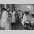 Four technicians and a blood-test patient in hospital laboratory at Granada incarceration camp (ddr-csujad-14-47)