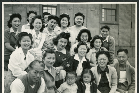 Photograph of a group of people posing in front of the Manzanar hospital (ddr-csujad-47-210)